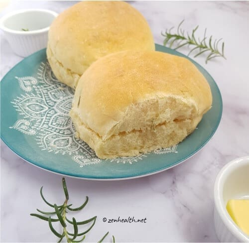 Two baked bread rolls with rosemary and butter